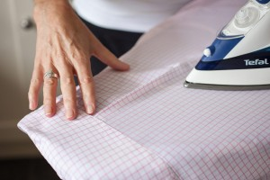 Gents pink check shirt being ironed